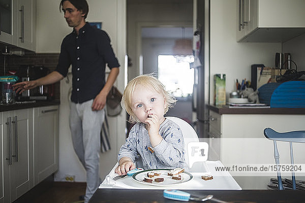 Portrait of blond baby boy eating while sitting on high chair at kitchen with father in background