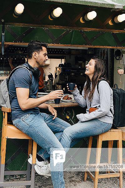 Lächelnde Freunde in voller Länge  die Kaffeetassen in der Hand halten  während sie an einem Imbissstand in der Stadt sitzen