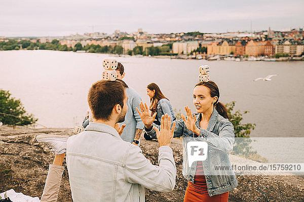 Männliche und weibliche Freunde spielen Balancierspiele  während sie auf einem Feld am See stehen