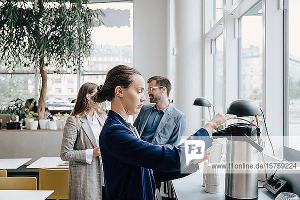Seitenansicht einer Geschäftsfrau  die Kaffee trinkt  während die Kollegen im Hintergrund diskutieren