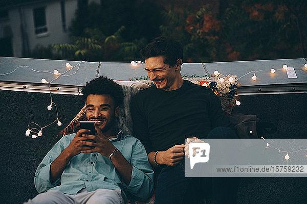 Lächelnde männliche Freunde schauen auf ein Smartphone und sitzen während einer Dachparty in der Stadt auf der Terrasse