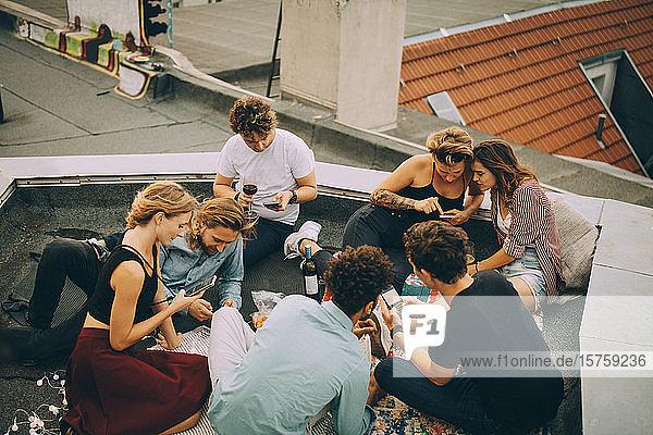Hochwinkelansicht von Freunden  die beim Feiern auf dem Dach mit Mobiltelefonen abgelenkt werden