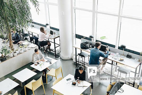 Schrägansicht von Geschäftskollegen  die am Schreibtisch im Coworking Space arbeiten