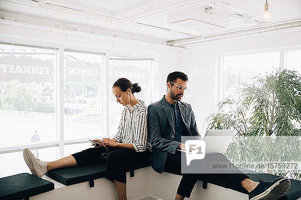 Männliche und weibliche Kollegen nutzen Technologien  während sie im kreativen Büro auf dem Flur sitzen
