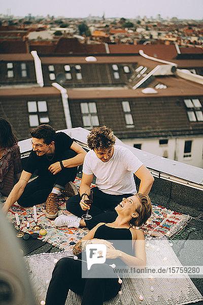 Schrägaufnahme von Freundinnen und Freunden  die sich während der Party auf der Terrasse unterhalten