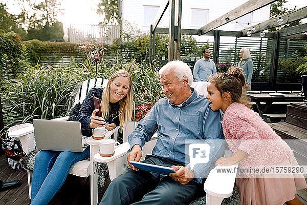 Lächelnde Familie nutzt digitale Technologie  während sie am Wochenende im Hinterhof sitzt