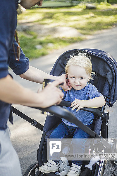 Midsection of man touching son sitting on baby carriage at public park
