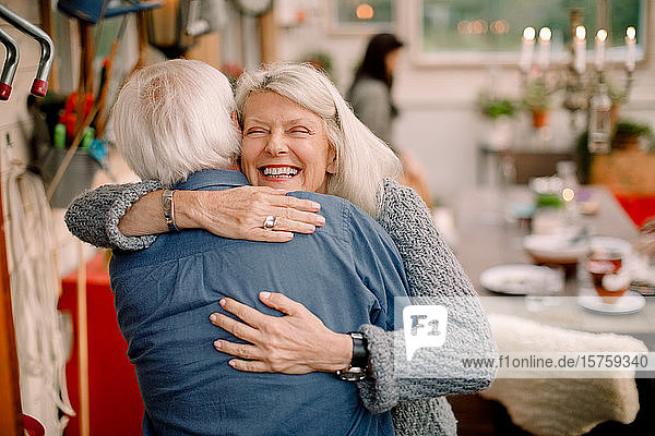 Glückliche ältere Frau umarmt Mann  während sie zu Hause steht