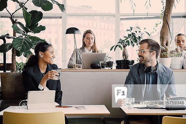 Lächelnde Kollegen unterhalten sich  während sie am Coworking Space sitzen