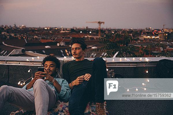Nachdenklicher Mann sitzt mit einem Freund zusammen und benutzt ein Mobiltelefon auf einer Terrasse in der Stadt