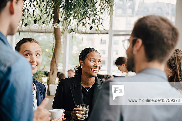 Lächelnde männliche und weibliche Kollegen diskutieren während der Kaffeepause