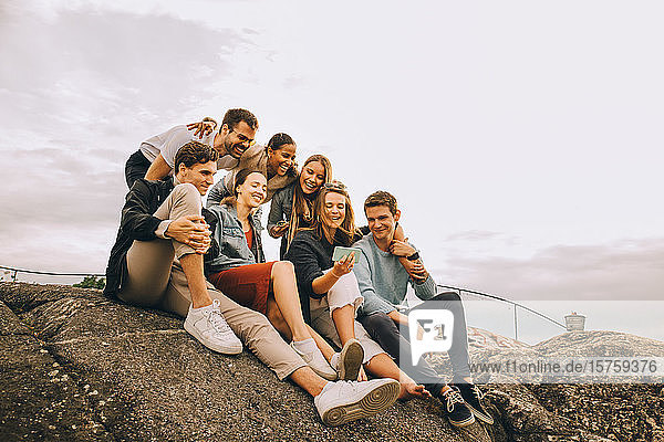 Happy male and female friends looking at mobile phone while sitting on rock formation against sky