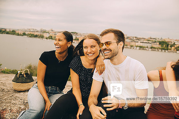 Cheerful friends looking away while sitting together on rock formation against lake