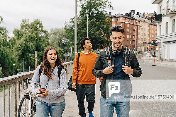 Lächelnde Freunde gehen auf der Straße  während sie im Urlaub die Stadt erkunden