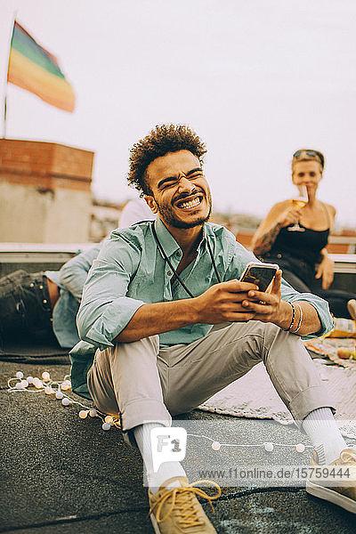 Fröhlicher junger Mann sendet SMS auf Smartphone  während er eine Party auf der Terrasse genießt