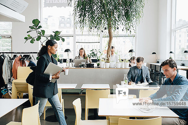 Geschäftsfrau mit Laptop beim Gehen  während Kollegen am Schreibtisch im Coworking Space arbeiten