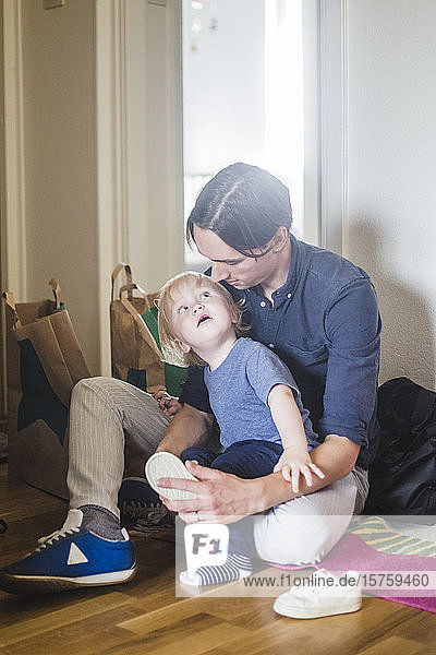 Baby boy looking at father assisting in wearing shoes