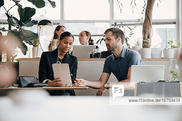Kreativprofis diskutieren über digitales Tablet am Büroschreibtisch