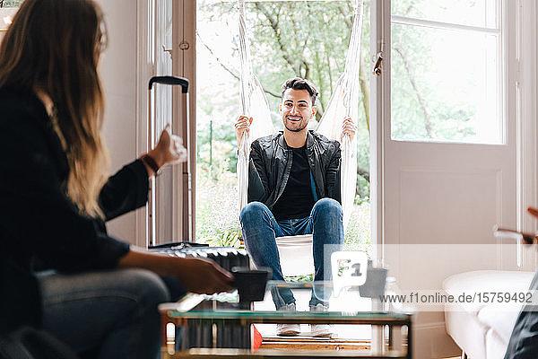 Junge Frau im Gespräch mit einem Freund  der im Wohnzimmer in Schaukel sitzt