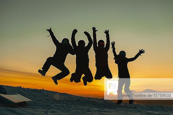 Freunde springen vor Freude gegen den Sonnenuntergang  Karpaten  Ukraine