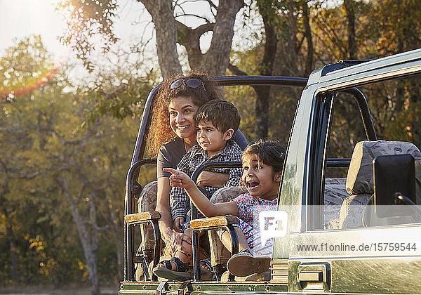 Mutter und Kinder genießen die Natur vom Geländewagen aus