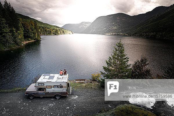 Freunde genießen die Aussicht auf den See auf der Spitze des Wohnmobils  Cathedral Grove  Britisch-Kolumbien  Kanada