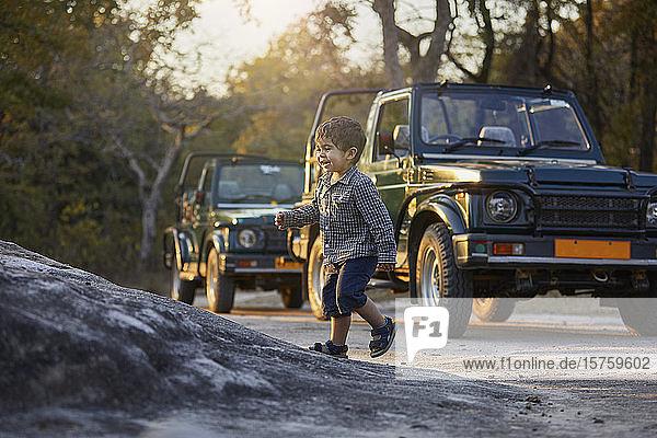 Kleiner Junge erkundet die Natur  Geländewagen im Hintergrund