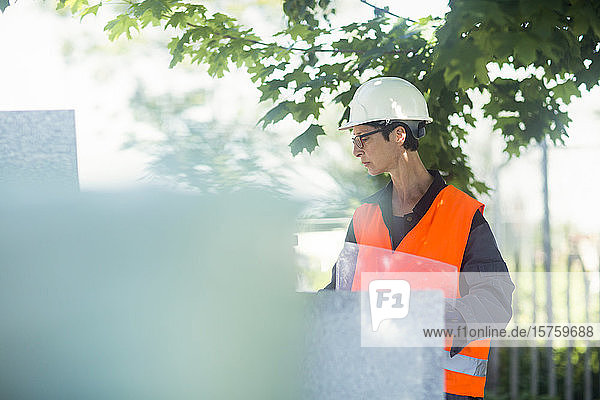 Woman working outdoors in a high vis jacket and safety hard hat.