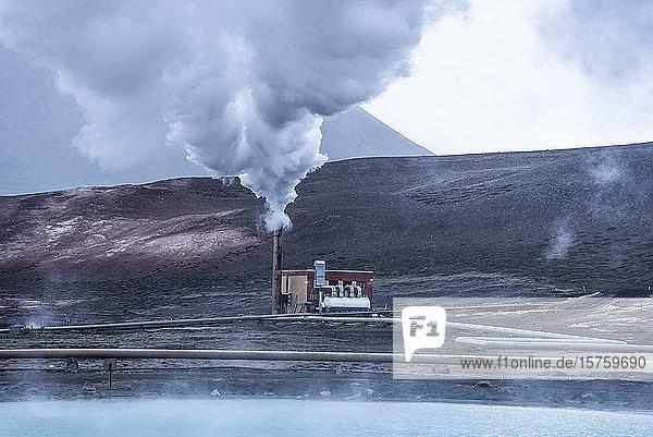 Rauch  der aus dem Schornstein einer Fabrik auf der kahlen Landschaft aufsteigt  Island