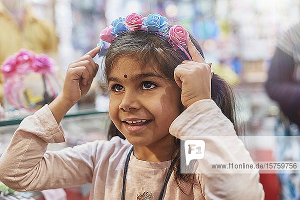 Kleines Mädchen probiert auf dem Basar Haarband mit Rosen an