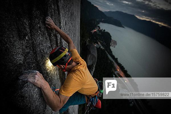 Eine Person trad klettert nachts  Blick auf die Landschaft unterhalb von Squamish  Britisch-Kolumbien  Kanada
