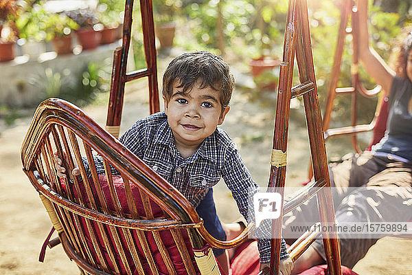 Kleiner Junge klettert auf Rattanschaukel