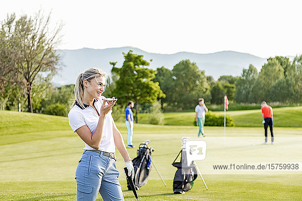 Woman talking on smartphone on golf course  friends playing golf in background