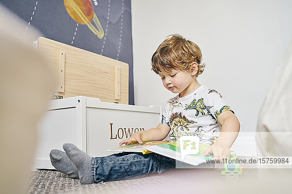 Toddler reading book in room