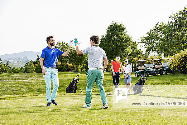 Friends giving high five on golf course  couple watching in background
