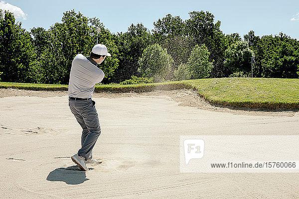 Mann spielt Golf auf dem Golfplatz