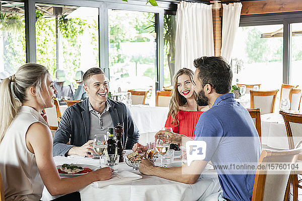 Friends talking at dining table in restaurant