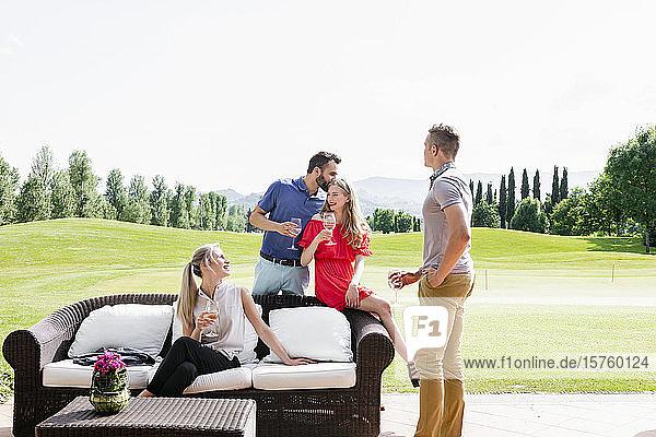 Freunde genießen Wein und unterhalten sich auf dem Sofa auf dem Golfplatz