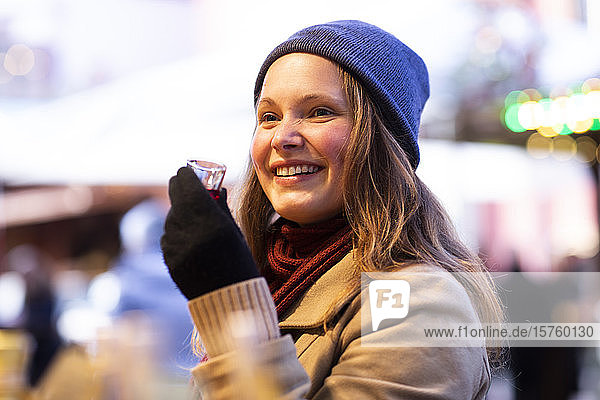 Woman holding small glass of beverage  Christmas Market  Freiburg  Deutschland