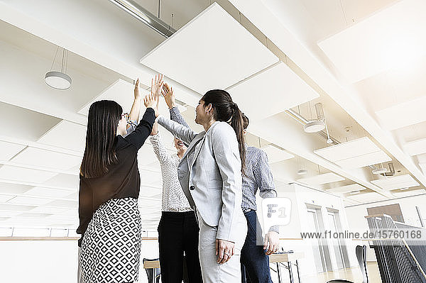 Kollegen  die sich einen High-Five-Moment im Amt teilen
