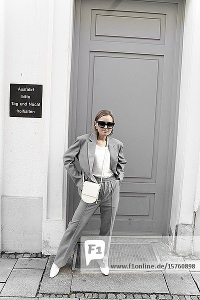 Fashionable woman in gray suit  standing in front of door. Munich  Germany.