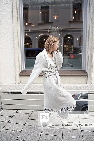 Fashionable woman standing beside mirror on the street. Munich  Germany.