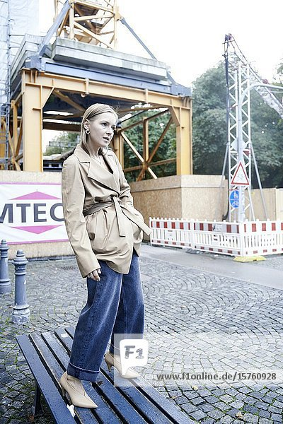 Fashionable woman standing on bench. Munich  Germany.