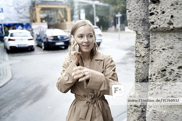 Busy woman calling with phone on the street. Munich  Germany.