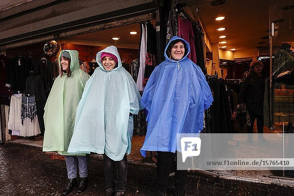 Tel Aviv  Israel  Pedestrian tourists caught in heavy rain at the Carmel market wearing ponchos.