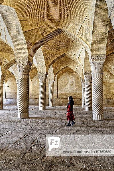 Iranian woman walking through the prayer hall with Shabestan pillars  Vakil Mosque  Shiraz  Fars Province  Iran.
