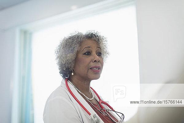 Senior female doctor making rounds  talking in hospital Senior female doctor making rounds, talking in hospital