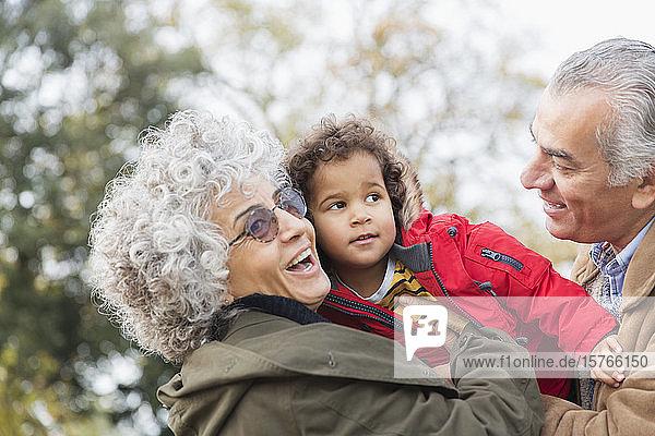 Affectionate grandparents hugging grandson