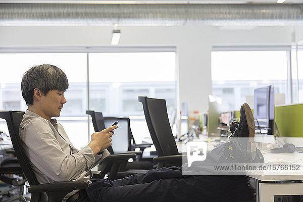 Businessman using smart phone with feet up on office desk