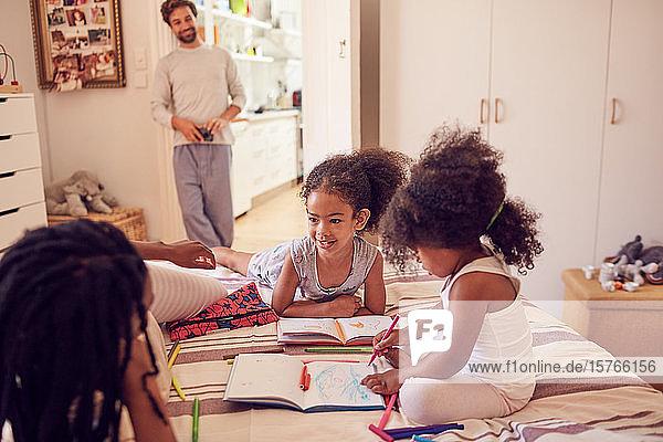 Junge Familie beim Malen auf dem Bett
